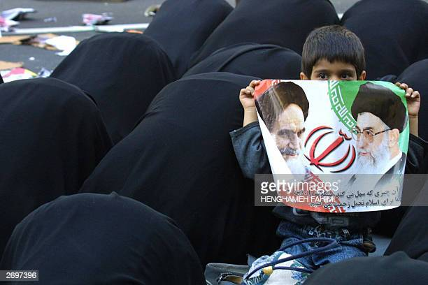 Iranian protesters pray after a demonstration as a little boy holds up a poster of the late Iranian leader Ruhollah Khameini and Iranian supreme...