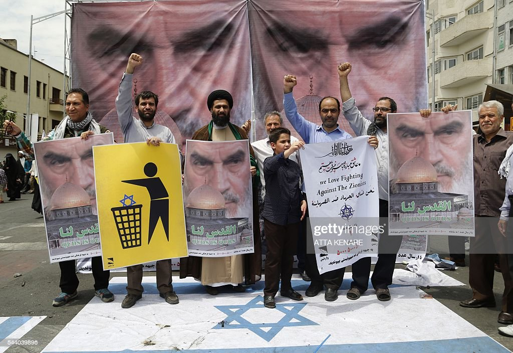 Iranian protestors hold anti-Israeli placards with portraits of late revolutionary leader Ayatollah Ruhollah Khomeini during a parade marking al-Quds (Jerusalem) Day in Tehran on July 01, 2016. Tens of thousands joined pro-Palestinian rallies in Tehran, as the annual Quds Day protests take on broader meaning for a region mired in bitter disputes and war. KENARE