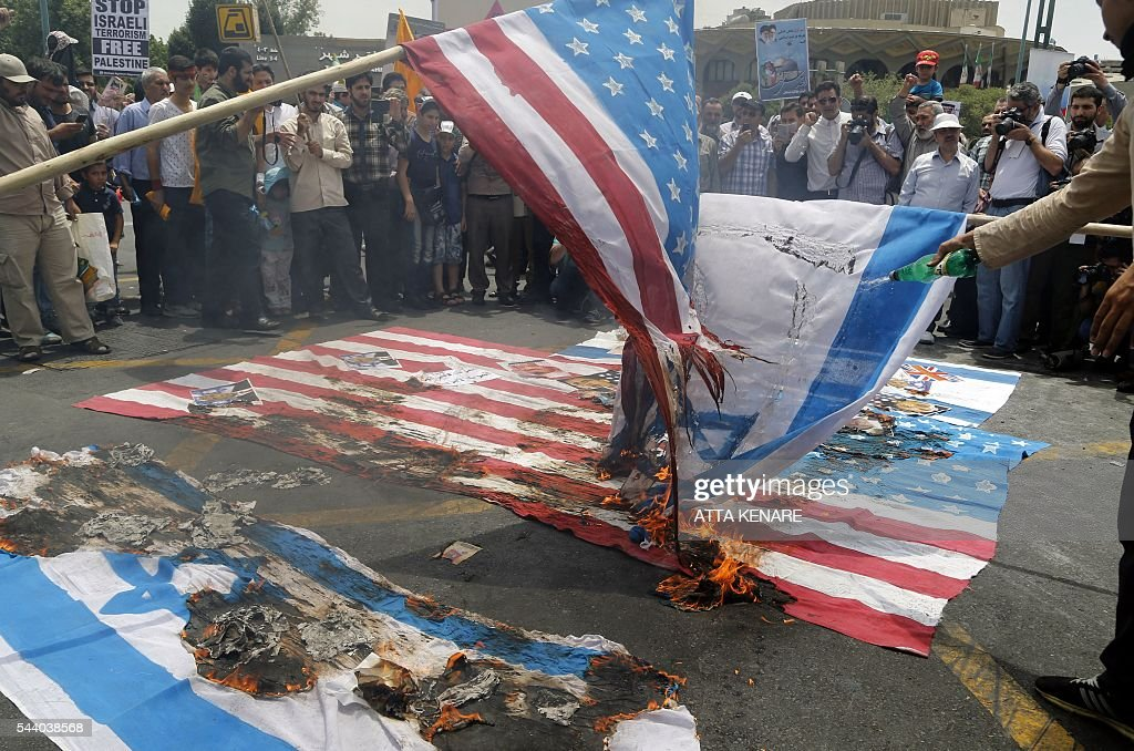 Iranian protestors set US and Israeli flags afire during a parade marking al-Quds (Jerusalem) Day in Tehran on July 01, 2016. Tens of thousands joined pro-Palestinian rallies in Tehran, as the annual Quds Day protests take on broader meaning for a region mired in bitter disputes and war. KENARE