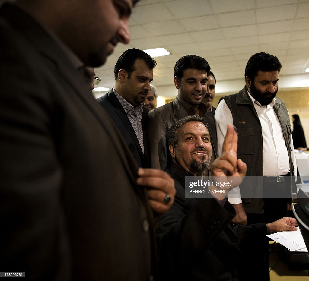 Iranian reformist MP Mostafa Kavakebian (bottom) flashes a 'V' sign for victory as he registers his candidacy for the upcoming presidential election at the interior ministry in Tehran on May 7, 2013. Iran began a five-day registration period for candidates in Iran's June 14 presidential election, with a string of conservative hopefuls in the running but with key reformists yet to come forward, media reports said. AFP PHOTO/BEHROUZ MEHRI