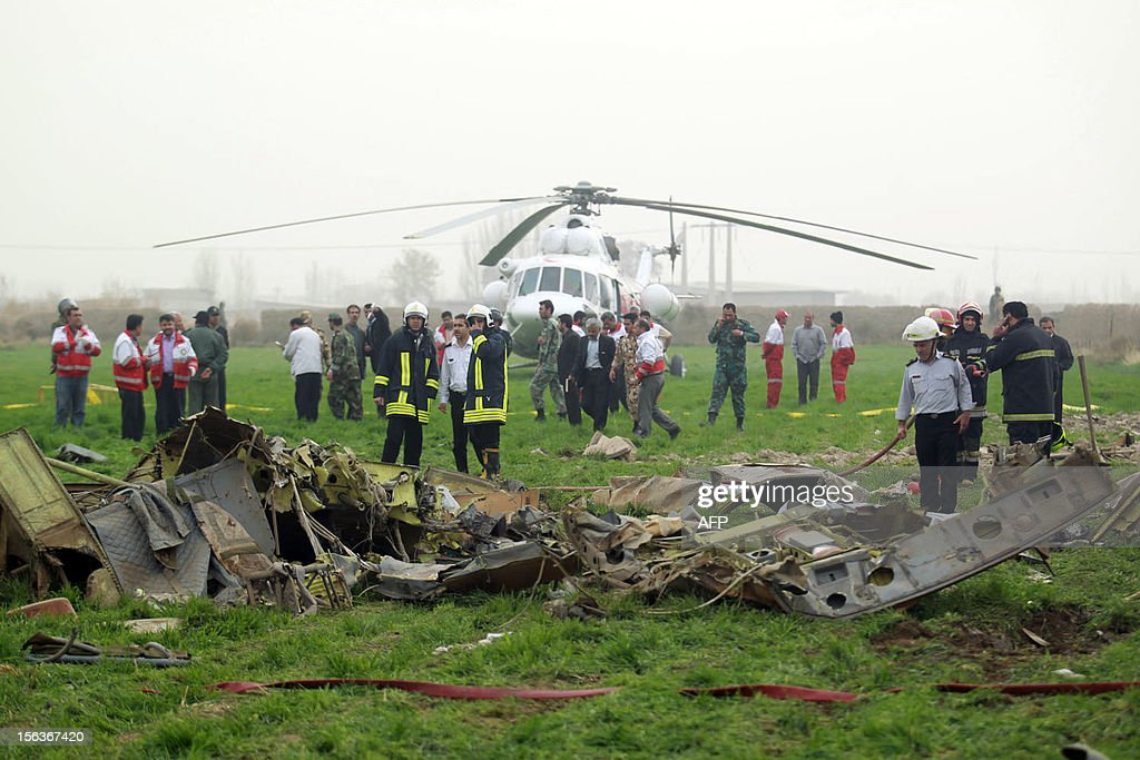 Iranian rescuers inspect the debris on a helicopter that crashed on November 14, 2012, close to Mashhad. Ten people were killed when the rescue helicopter ferrying wounded people from a vehicle accident to hospital hit power lines and crashed to the ground in northeastern Iran, media reported.