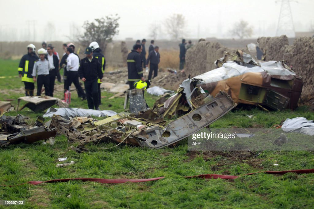 Iranian rescuers look at the debris on a helicopter that crashed on November 14, 2012, close to Mashhad. Ten people were killed when the rescue helicopter ferrying wounded people from a vehicle accident to hospital hit power lines and crashed to the ground in northeastern Iran, media reported. AFP PHOTO/MEHR NEWS/MEHDI BOLOURIAN