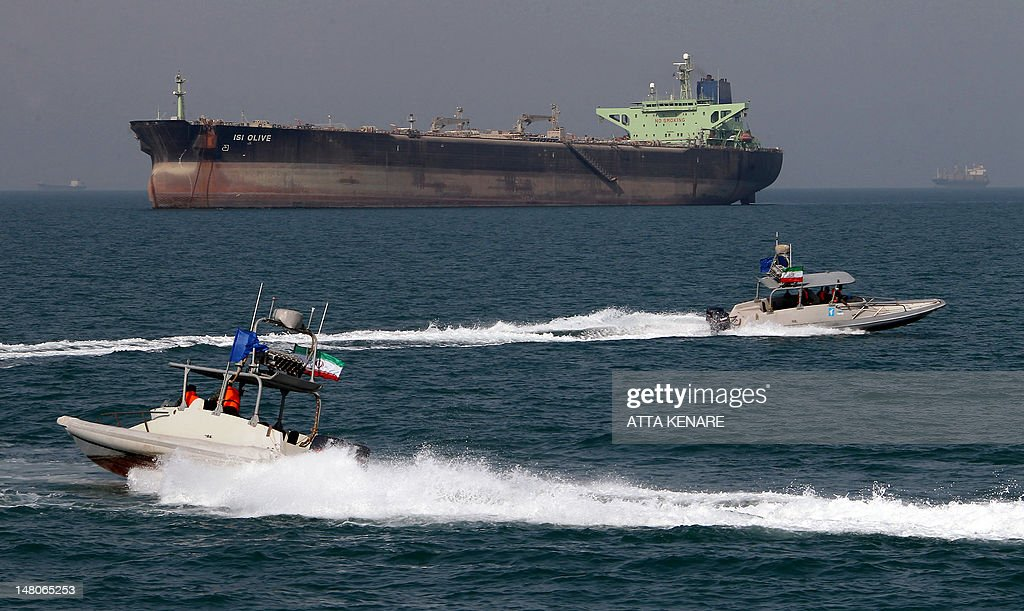 Iranian Revolutionary Guard speedboats cruise past an oil tanker off the port of Bandar Abbas, southern Iran, on July 2, 2012. Iran has come up with several methods to foil the European insurance embargo on ships loaded with its crude, a sanction which may harm its vital exports as much as the EU oil embargo itself.