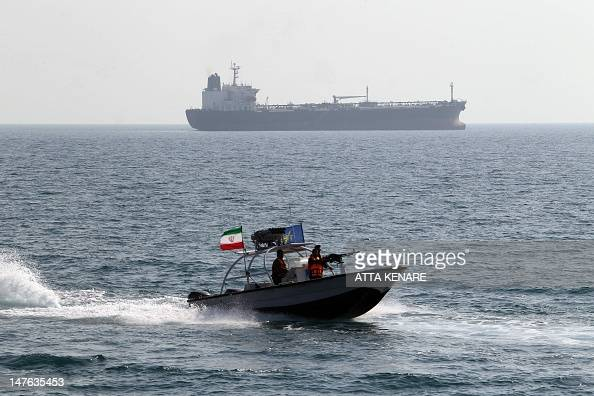 Iranian Revolutionary Guards drive a speedboat in front of an oil tanker during a ceremony to commemorate the 24th anniversary of the downing of Iran...