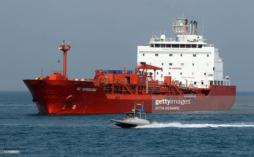 Iranian Revolutionary Guards drive a speedboat in front of an oil tanker from Honk Kong during a ceremony to commemorate the 24th anniversary of the...