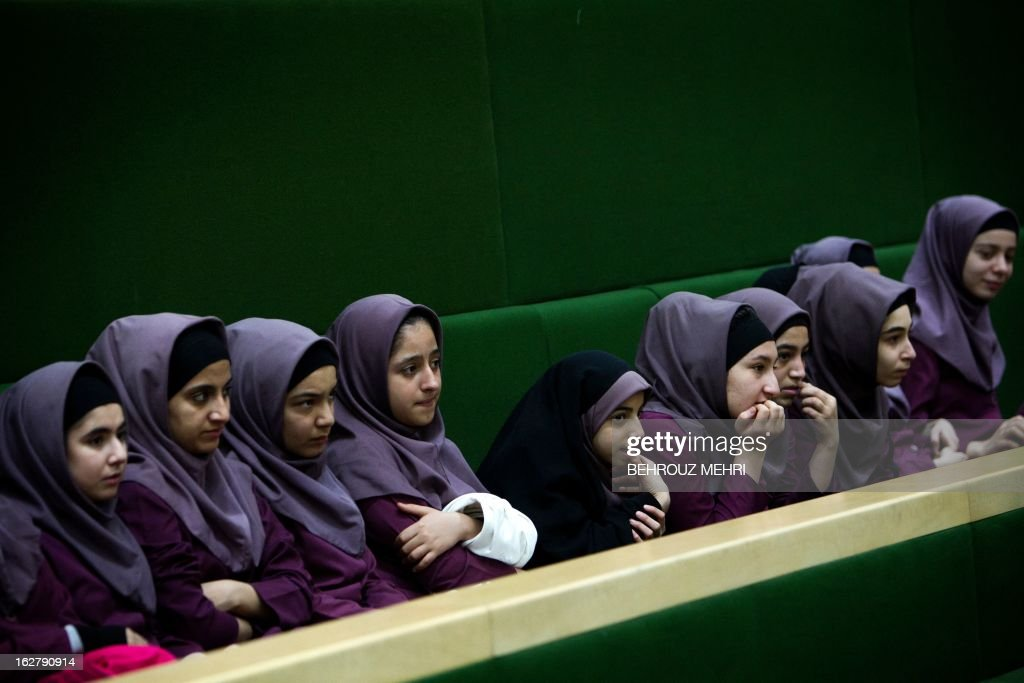 Iranian school girls observe Members of Parliament (MP) discussing a draft to limit photographer's and cameramen's access to cover parliament's open sessions in Tehran on February 27, 2013. The debate took part on the sidelines of a parliamentary session to discuss the annual budget bill which is being presented by the government.