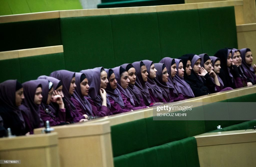 Iranian school girls observe Members of Parliament (MP) discussing a draft to limit photographer's and cameramen's access to cover parliament's open sessions in Tehran on February 27, 2013. The debate took part on the sidelines of a parliamentary session to discuss the annual budget bill which is being presented by the government. AFP PHOTO/BEHROUZ MEHRI