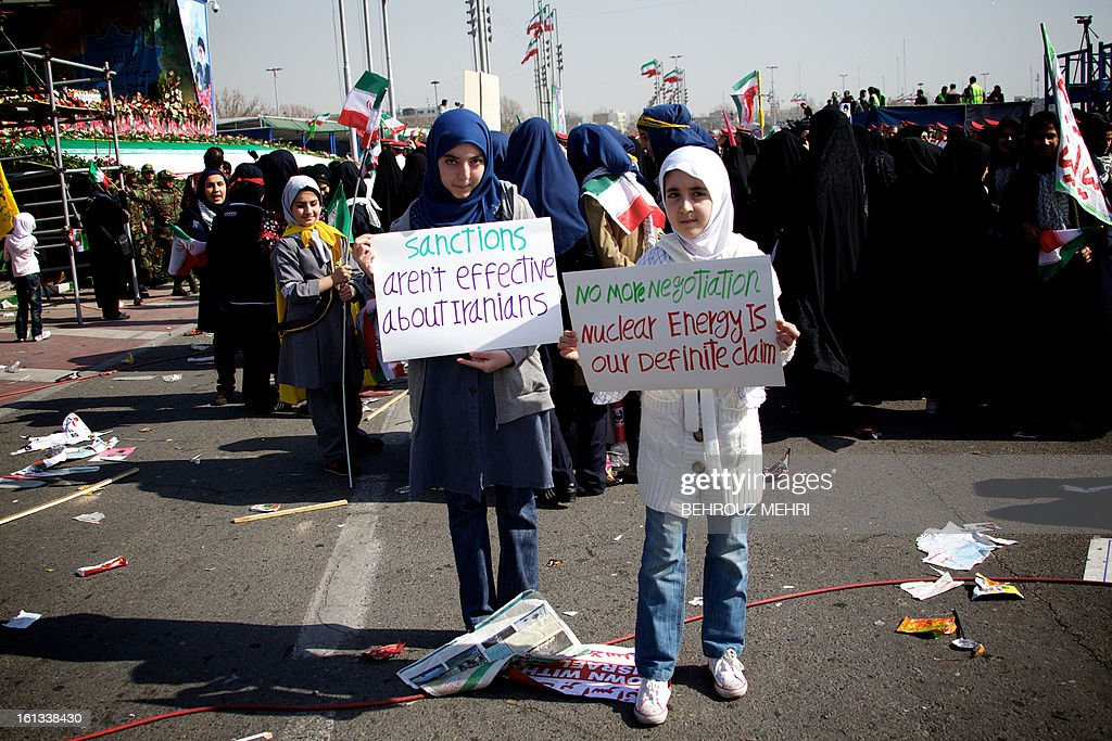 Iranian school girls pose with banners supporting Iran's nuclear program during a rally in Tehran's Azadi Square (Freedom Square) to mark the 34th anniversary of the Islamic revolution on February 10, 2013. Hundreds of thousands of people marched in Tehran and other cities chanting 'Death to America' and 'Death to Israel' as Iran celebrated the anniversary of the ousting of the US-backed shah. AFP PHOTO/BEHROUZ MEHRI