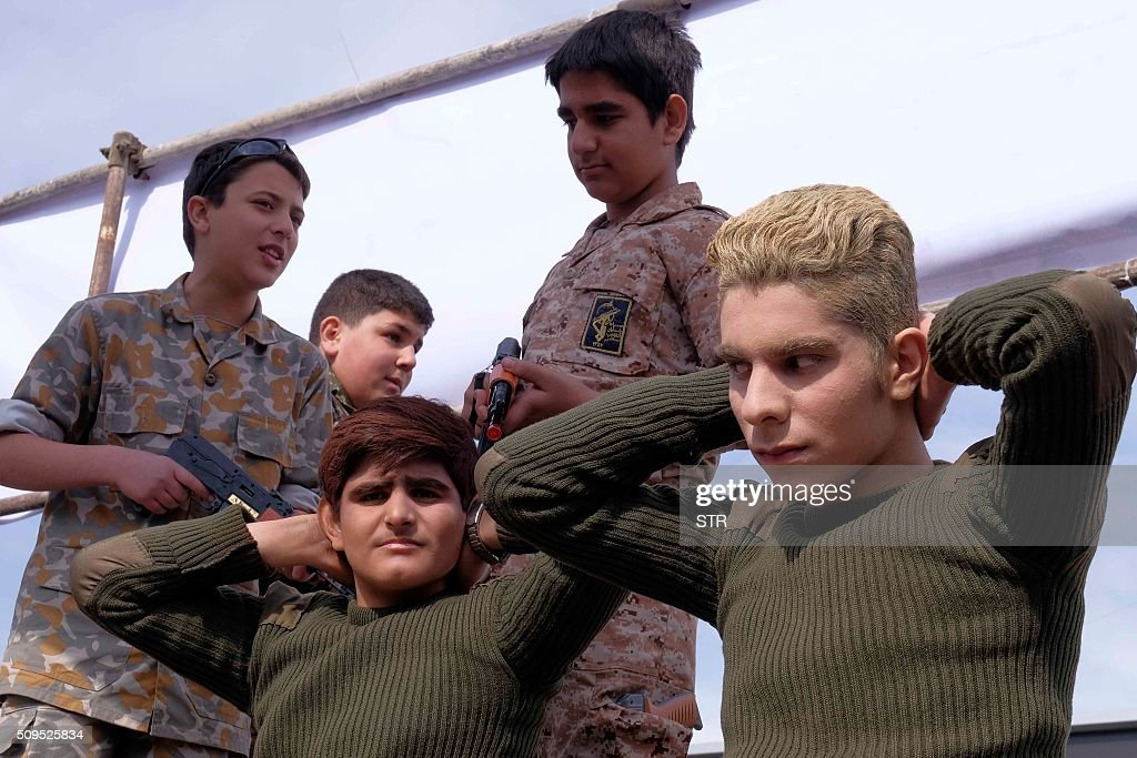 Iranian schoolboys reenact the detention of US sailors by Iran's Revolutionary Guards during celebrations marking the 37th anniversary of the Islamic revolution on February 11, 2016 in Tehran. Touted domestically as proof of Iran's ability to defend its borders, the sailors were released within 24 hours, just days before the nuclear deal was finalised on January 16. Iranians waved 'Death to America' banners and took selfies with a ballistic missile as they marked 37 years since the Islamic revolution, weeks after Iran finalised a nuclear deal with world powers. / AFP / STR