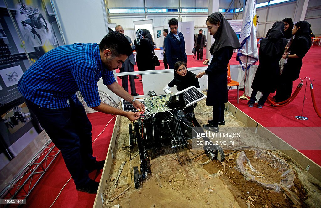 Iranian schoolgirls and their teachers work on a robot used in minning for minerals and natural resources during on the sideline of the Robo-Cup Iran Open 2013 in Tehran on April 5, 2013.