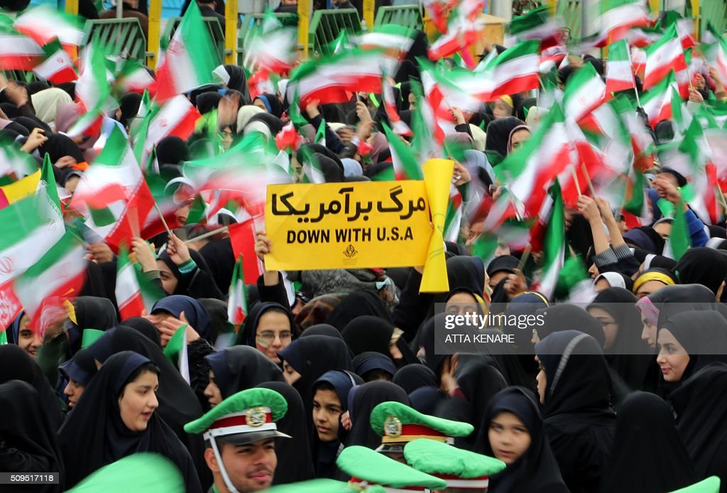 Iranian schoolgirls wave their national flag and hold an anti-US slogan during celebrations in Tehran's Azadi Square (Freedom Square) to mark the 37th anniversary of the Islamic revolution on February 11, 2016. / AFP / ATTA KENARE