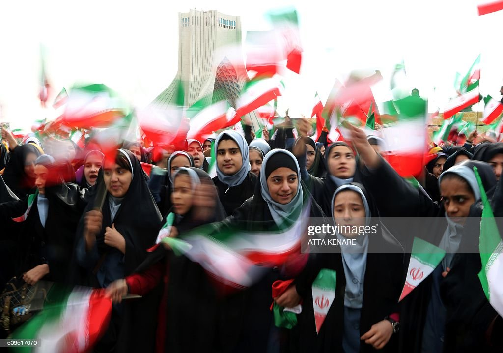 Iranian schoolgirls wave their national flag during celebrations in Tehran's Azadi Square (Freedom Square) to mark the 37th anniversary of the Islamic revolution on February 11, 2016. / AFP / ATTA KENARE