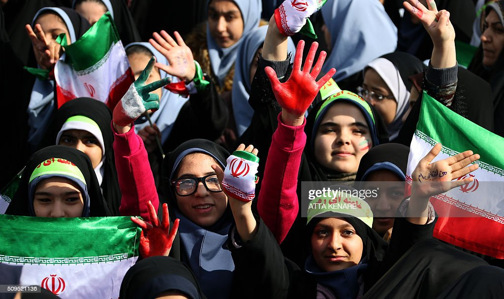 Iranian schoolgirls wave their national flag during celebrations in Tehran's Azadi Square (Freedom Square) to mark the 37th anniversary of the Islamic revolution on February 11, 2016. Iranians waved 'Death to America' banners and took selfies with a ballistic missile as they marked 37 years since the Islamic revolution, weeks after Iran finalised a nuclear deal with world powers. KENARE