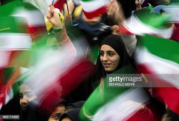 Iranian schoolgirls wave their national flag during the 36th anniversary of the Islamic revolution in Tehran's Azadi Square on February 11 2015...