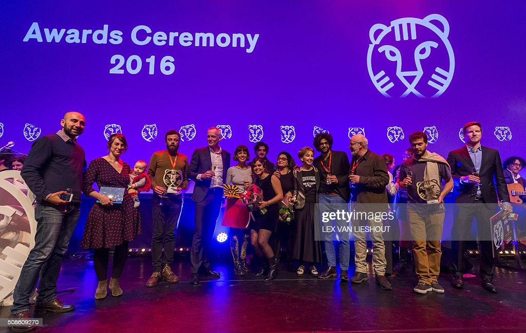Iranian screenwriter Babak Jalali (3rd L) poses, alongside other award winners, with the Hivos Tiger Award for the movie 'Radio Dreams' in Rotterdam on February 5, 2016, during the International Film Festival Rotterdam (IFFR). / AFP / ANP / Lex van Lieshout / Netherlands OUT