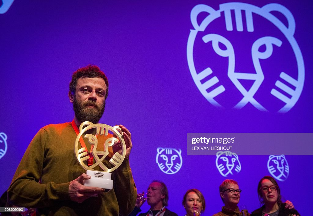 Iranian screenwriter Babak Jalali poses with the Hivos Tiger Award for the movie 'Radio Dreams' in Rotterdam on February 5, 2016, during the International Film Festival Rotterdam (IFFR). / AFP / ANP / Lex van Lieshout / Netherlands OUT