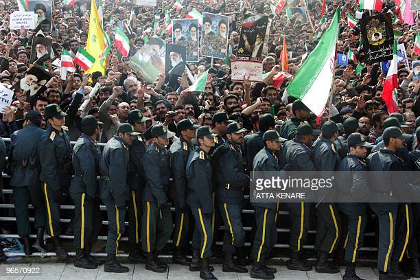 Iranian security forces stand guard as tens of thousands of Iranians gather in Azadi Square in southwestern Tehran to listen to a speech by President...