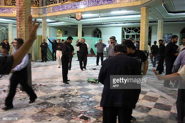 Iranian security personnel and civilians inspect the site of a bomb blast inside the Amir alMomenin mosque in the southeastern Iranian city of...