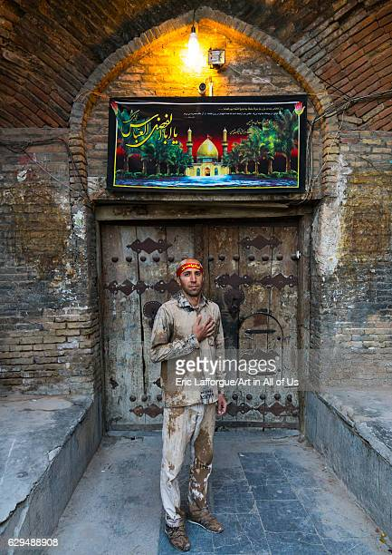 Iranian shiite muslim man standing in front of an old wooden door after rubbing mud on his clothes during the Kharrah Mali ritual to mark the Ashura...