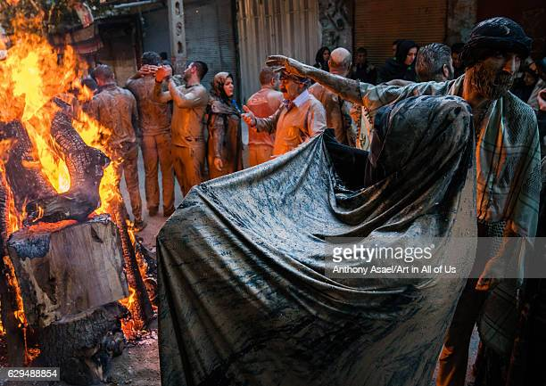 Iranian shiite muslim men and women gather around a bonfire after rubbing mud on their clothes during the Kharrah Mali ritual to mark the Ashura day...
