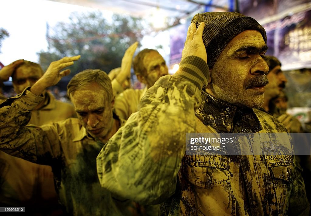 Iranian Shiite Muslims flagelate themselves after rubbing mud on their body early in the morning, during the 'Kharrah Mali' (Mud Rubbing) ritual to mark the Ashura religious ceremony in the city of Khorramabad, some 470 kms southwest of Tehran on November 25, 2012. 'Khrreh Mali' or 'Mud Rubbing' is a ritual that is held in the city of Khorramabad every year to commemorate the seventh century slaying of Prophet Mohammed's grandson Imam Hussein, in which Iranian men roll over in mud and dry themselves by gathering around the bonfires before flagellating themselves.