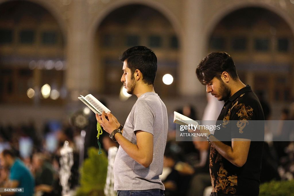 Iranian Shiite Muslims pray at the Imam Khomeini grand mosque in the capital Tehran in the early hours of July 27, 2016 in commemoration of the death of the seventh century Imam Ali bin Abi-Taleb and in preparation for Laylat al-Qadr -- a high point during Ramadan when the Koran, Islam's holy book, was revealed to Prophet Mohammed by archangel Gabriel. Imam Ali is the first Shiite Imam and fourth caliph to succeed Prophet Mohammed, his cousin and father-in-law. / AFP / ATTA
