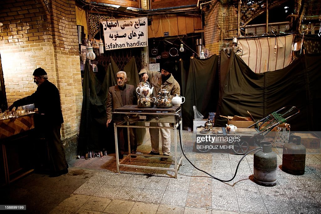 Iranian Shiite Muslims prepare some tea for the mourners at Tehran's Grand Bazaar, on January 3, 2013 during the Arbaeen religious festival which marks the 40th day after Ashura, commemorating the seventh century killing of Prophet Mohammed's grandson, Imam Hussein. AFP PHOTO/BEHROUZ MEHRI