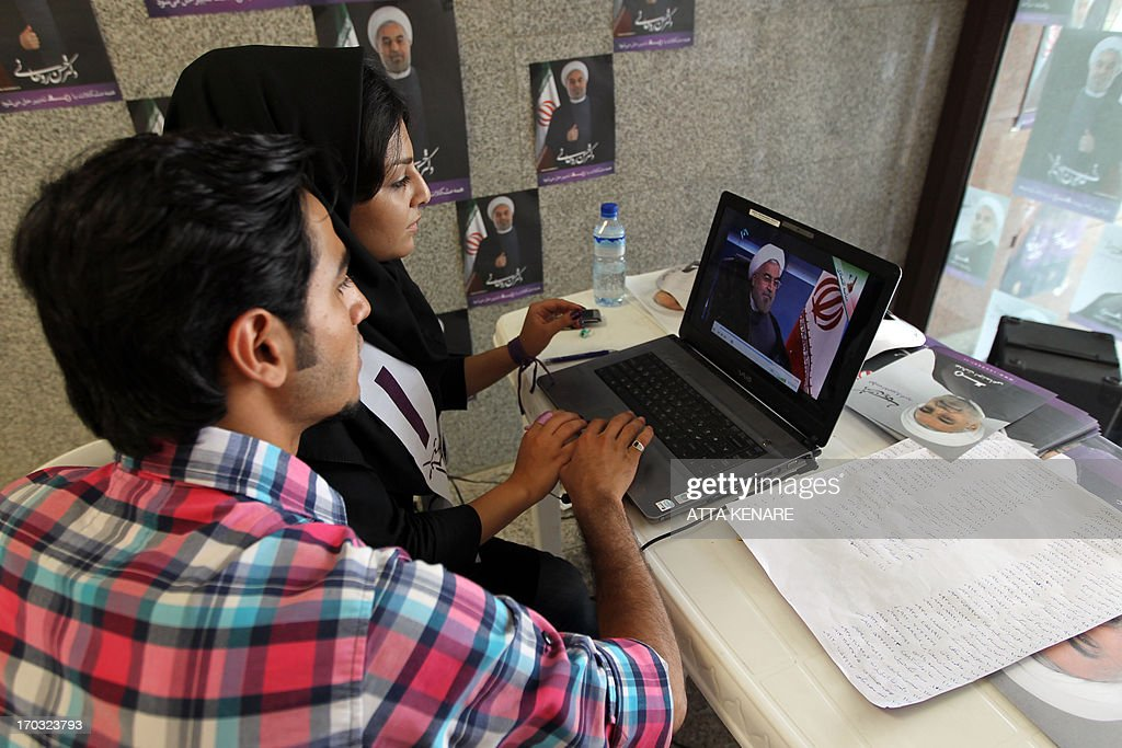 Iranian supporters of Hassan Rowhani, moderate presidential candidate and former top nuclear negotiator, work on a laptop in one of his campaign offices in Tehran on June 11, 2013. Iran elects on June 14, 2013 a successor to President Mahmoud Ahmadinejad, whose eight years in office have been marked by stiff Western sanctions over Tehran's controversial nuclear drive and the economic turmoil they have caused. AFP PHOTO/ATTA KENARE