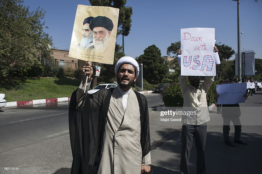 Iranian supporters of the Basiji militia raise up placards as Iranian president Hassan Rouhani's motorcade leaves Mehrabad Airport on September 28, 2013 in Tehran, Iran. Hardline Islamists gathered outside the airport to chant ''Death to America'' and ''Death to Israel'' but they were outnumbered by supporters of President Rouhani who shouted 'Thank you Rouhani.' Iranian newspapers hailed the first contact between presidents Rouhani and Obama but warned that Israel would seek to impede the historic opening to Washington.