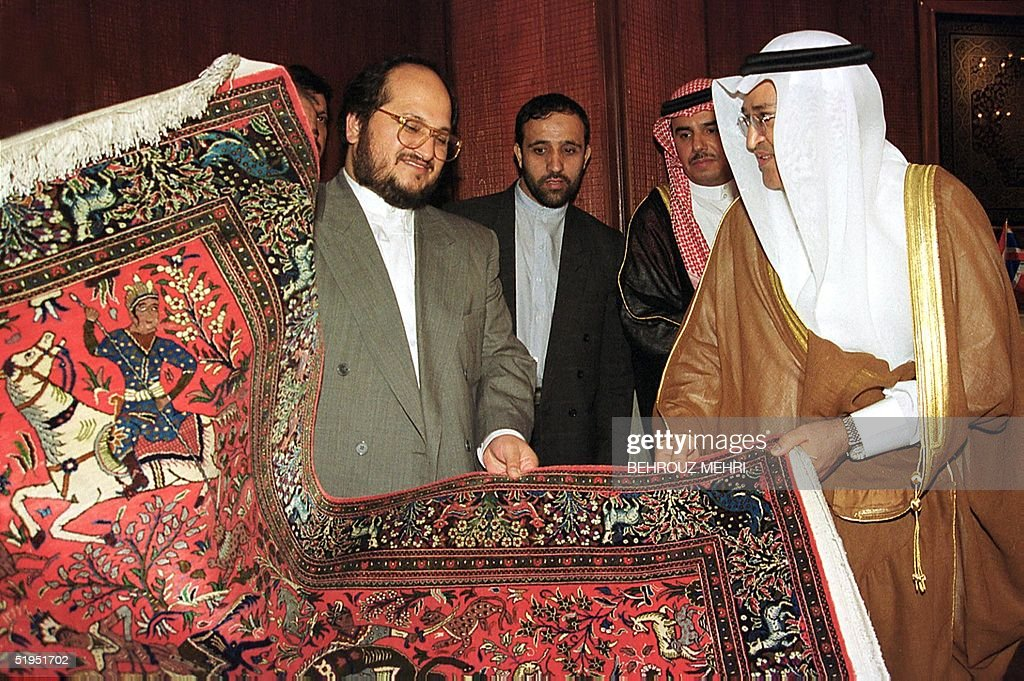 Iranian Trade Minister Mohammad Hossein Shariatmadari presents an Iranian made carpet to Saudi Industry and Electricity Minister Hashem bin Abdullah bin Hashem Yamani at Iran's International Trade Fair in Tehran 05 October 1999. The Saudi minister arrived in Tehran 04 October 1999 at the head of a 120-strong delegation for the opening of the biggest international trade fair in Iran since the 1979 Islamic revolution.