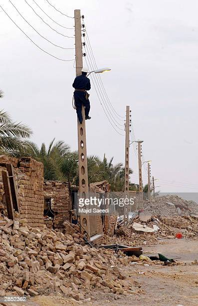 Iranian utility workers repair power lines along a street January 8 2004 in Bam Iran It has been estimated that 90 percent of Bam's building were...