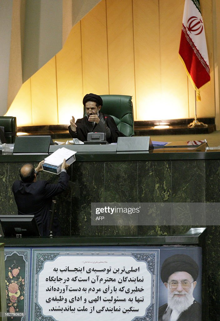 Iranian Vice President in charge of parliament affairs, Lotfollah Forouzandeh (bottom), hands over the annual budget bill to Deputy parliament speaker, Hassan Abutorabi Fard, during an open session in parliament in Tehran on February 27, 2013.