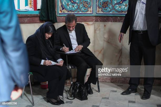Iranian vicepresident Eshaq Jahangiri and his wife prepare to cast their ballots for the presidential elections at a polling station in Tehran on May...