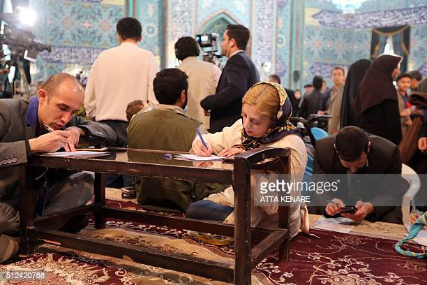 Iranian voters check a list of candidates for both parliamentary elections and the Assembly of Experts at a mosque being used as a polling station in...