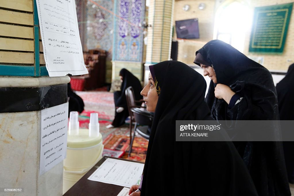 Iranian voters check a list of candidates to vote in the second round of parliamentary elections at a polling station in the town of Robat Karim, some 40 kms southwest of the capital Tehran, on April 29, 2016. Iranians started voting in second round elections for almost a quarter of parliament's seats, the latest political showdown between reformists and conservatives seeking to influence the country's future. Polling stations opened at 8:00 am (0330 GMT) for the ballot which is taking place in 21 provinces, but not Tehran, because no candidate in 68 constituencies managed to win 25 percent of votes cast in initial voting on February 26. Reformists who backed moderate President Hassan Rouhani made big gains in the first round following Iran's implementation of a nuclear deal with world powers, which lifted sanctions blamed for long hobbling the economy. Conservative MPs, including vehement opponents of the West who openly criticised the landmark agreement that reined in Iran's atomic programme, lost dozens of seats and were wiped out in Tehran where reformists won all 30 places in parliament. / AFP / ATTA