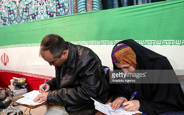 Iranian voters register before casting their vote for both parliamentary elections and the Assembly of Experts at a polling station in Tehran on...