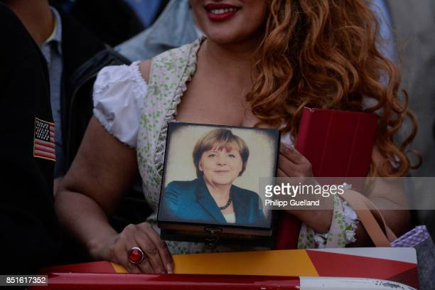 Iranian Woman in traditional bavarian dress with a purse showing Angela Merkel's portrait stands at a barrier during Chancellor Angela Merkel's last...