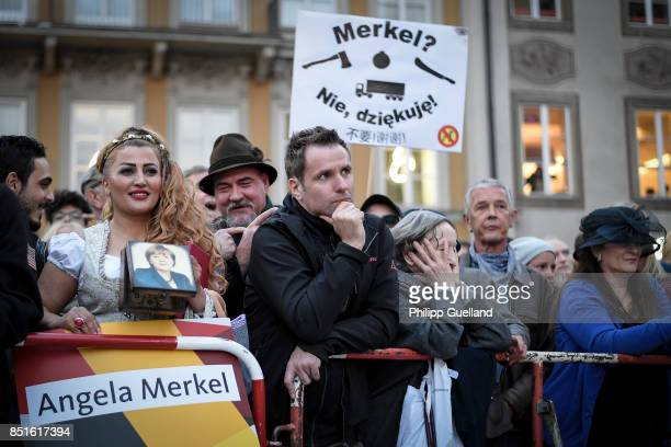 Iranian Woman in traditional bavarian dress with a purse showing Angela Merkel's portrait stands in front of protesters at Chancellor Angela Merkel's...