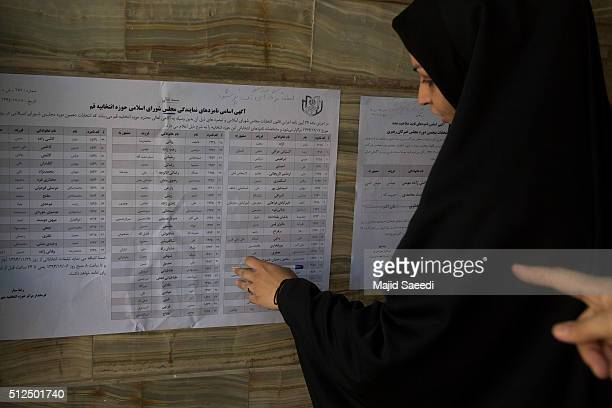 Iranian woman searches the list of candidates during the parliamentary and Experts Assembly elections at a polling station on February 26 2016 in Qom...