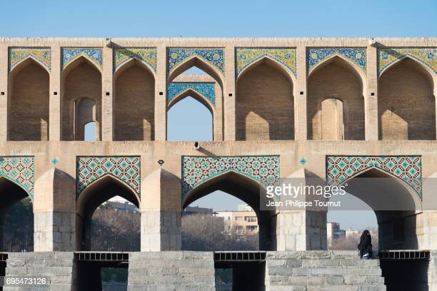 Iranian woman wearing traditional chador sitting on the steps on Khaju Bridge, Isfahan, Iran