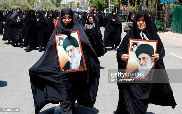 Iranian women carry portraits of current and former Iranian supreme leaders Ayatollah Khamenei and Khomeini at a demonstration after Friday prayers...