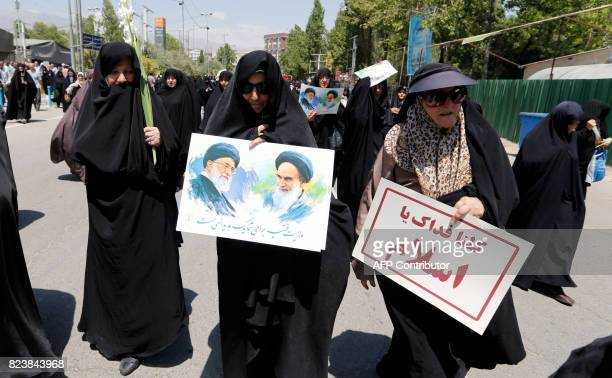 Iranian women carry portraits of former and current Iranian supreme leaders Ayatollah Khomeini and Khamenei with a slogan reading in Arabic 'we...