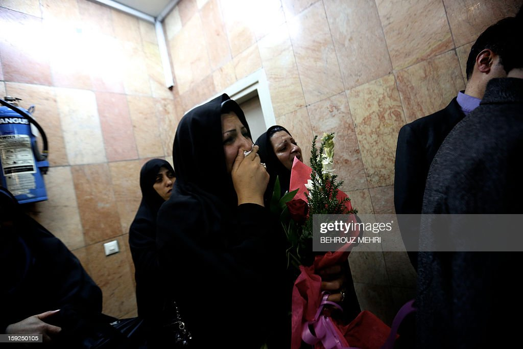 Iranian women cry as they see their relative who has been held hostage, alongside 48 other Iranians, by Syrian rebels since early August 2012, as he arrives at Tehran's Mehrabad airport on January 10, 2013. The rebels agreed to swap the 48 Iranians, described by the Islamic republic as pilgrims but by the rebels and Washington as members of Iran's elite Revolutionary Guards, for more than 2,000 detainees held by the Syrian regime. AFP PHOTO / BEHROUZ MEHRI