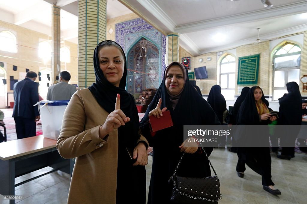 Iranian women display their ink-stained fingers after casting their ballot to vote in the second round of parliamentary elections at a polling station in the town of Robat Karim, some 40 kms southwest of the capital Tehran, on April 29, 2016. Iranians started voting in second round elections for almost a quarter of parliament's seats, the latest political showdown between reformists and conservatives seeking to influence the country's future. Polling stations opened at 8:00 am (0330 GMT) for the ballot which is taking place in 21 provinces, but not Tehran, because no candidate in 68 constituencies managed to win 25 percent of votes cast in initial voting on February 26. Reformists who backed moderate President Hassan Rouhani made big gains in the first round following Iran's implementation of a nuclear deal with world powers, which lifted sanctions blamed for long hobbling the economy. Conservative MPs, including vehement opponents of the West who openly criticised the landmark agreement that reined in Iran's atomic programme, lost dozens of seats and were wiped out in Tehran where reformists won all 30 places in parliament. / AFP / ATTA