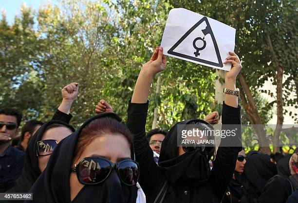 Iranian women hiding their faces not to be identified shout slogans during a protest in front of the judiciary building on October 22 2014 in Isfahan...