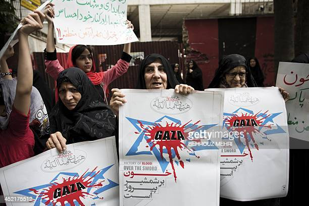 Iranian women hold up antiIsrael posters during a protest outside the United Nations offices in Tehran on July 15 held by a small group of...