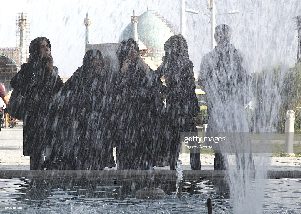 Iranian women in chadors gather by water fountains at the Naqsh-e Jahan Squareon August 17, 2012 in Isfahan, Iran.