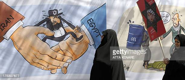 Iranian women look at a cartoon displayed during a parade marking AlQuds International Day in Tehran on August 2 2013 An initiative started by...