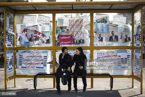 TOPSHOT Iranian women sit at a bus station decorated with electoral posters of the upcoming parliamentary elections in downtown Tehran on February 25...