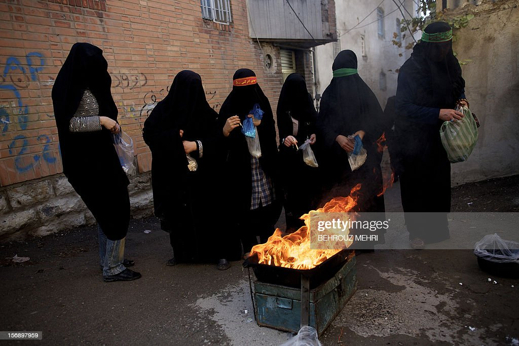 Iranian women stand next to burning candles during the 'Chehel Manbar' (Forty Pulpits) ritual a day before Ashura, in the city of Khorramabad, 470 kilometres southwest of Tehran on November 24, 2012. Traditionally, Iranian women of Khorramabad walk barefoot to light candles in 40 designated places in the city centre on the eve of the Ashura, which marks the seventh century slaying of the grandson of Prophet Mohammed, Imam Hussein. AFP PHOTO/BEHROUZ MEHRI